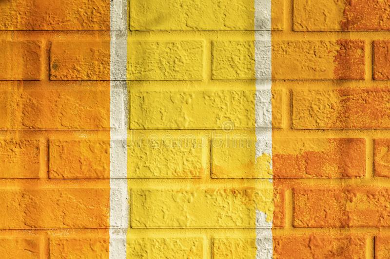 Bricks surface of wall, painted vertical lines in orange and yellow colors. Graphic grunge texture of wall. Abstract. Bright background royalty free stock images