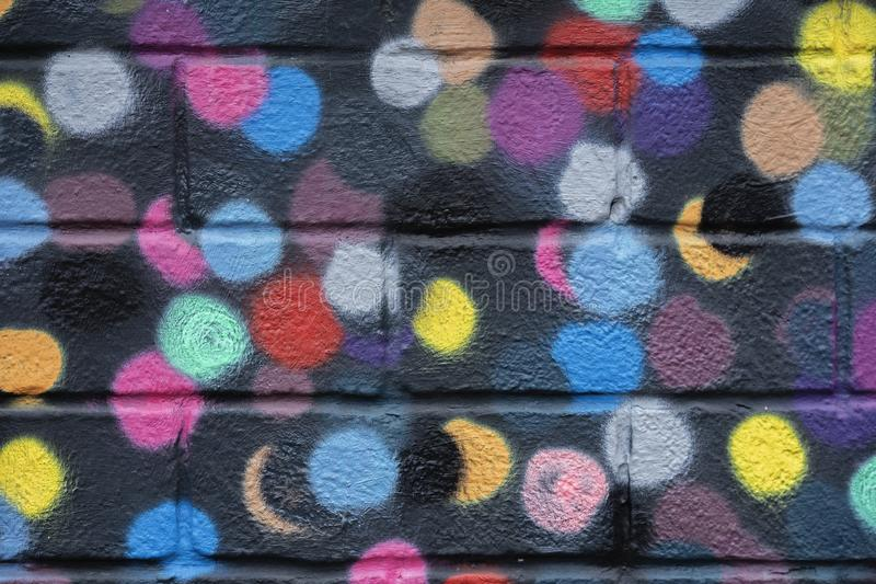 Bricks wall is decorated with bright abstract colored circles on black background closeup. Detail like as graffiti royalty free stock images