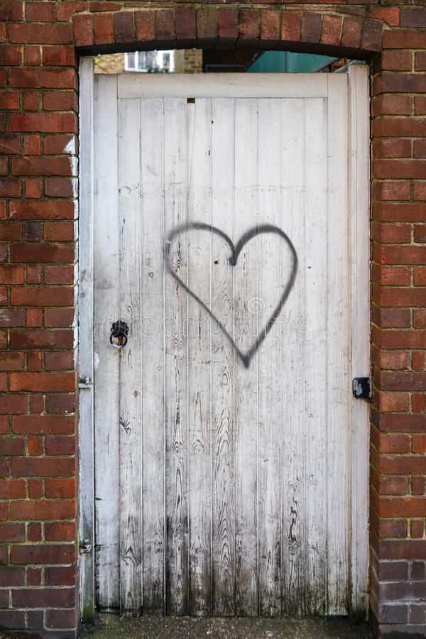 Bricks wall with old white boards door, black heart symbol sprayed on.  stock images