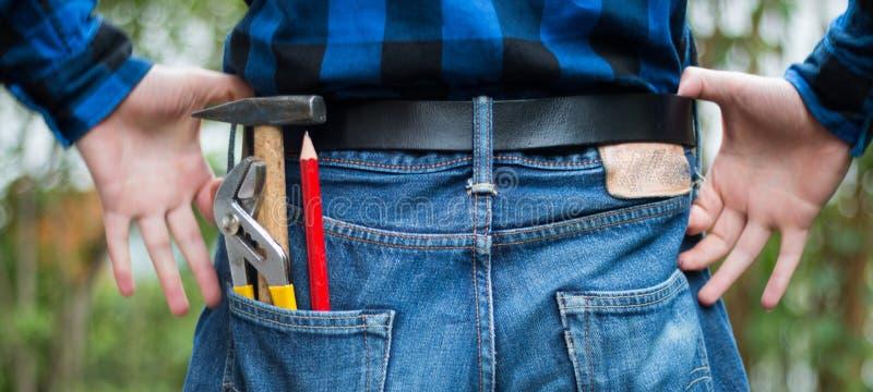 Bricoleur à la maison : Vue arrière d'un jeune homme avec le marteau, le crayon et la pince dans sa poche image libre de droits