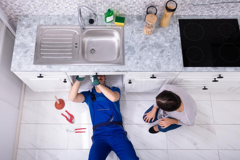 Bricoleur Lying On Floor r?parant l'?vier dans la cuisine photo libre de droits