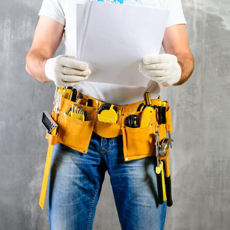 Bricoleur non identifié se tenant avec une ceinture d'outil avec le constructio image stock