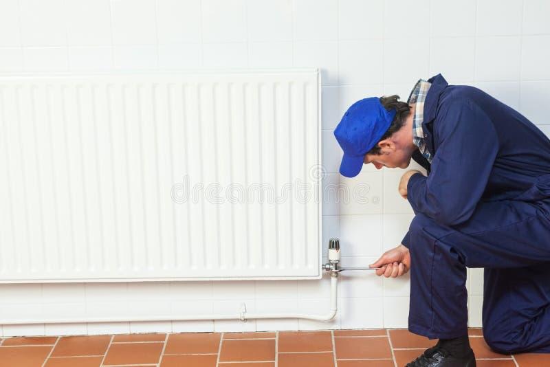 Bricoleur réparant un radiateur image stock