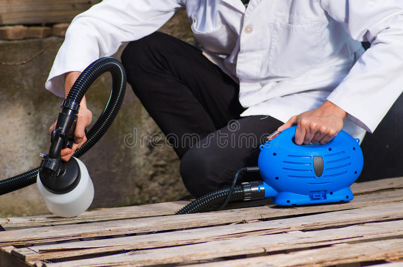 Bricoleur tenant dans le sien la main le jet de peinture, peinture de travailleur de la construction avec le pistolet de pulvéris photographie stock libre de droits