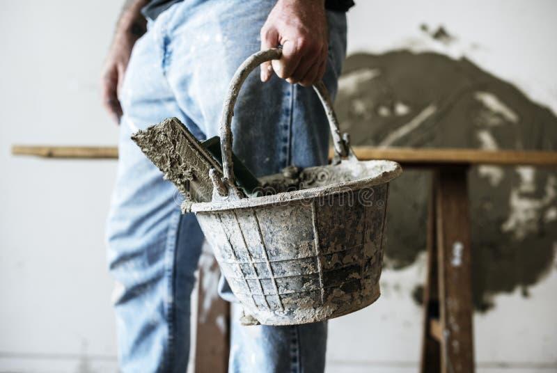 Bricoleur tenant le ciment de panier pour la construction photos libres de droits