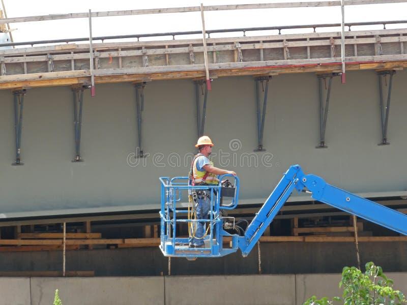 Bridżowy pracownik budowlany na estradowym dźwignięciu zdjęcie royalty free