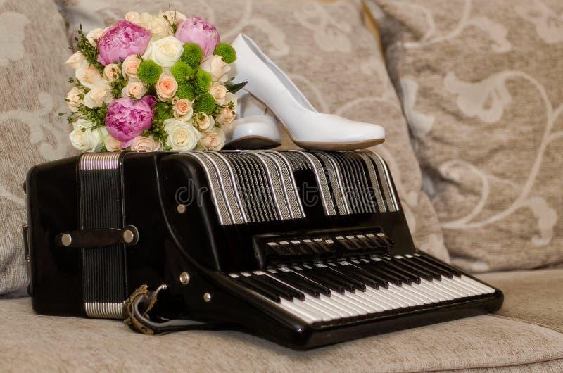 Bridal букет, ботинки и кольца на аккордеоне стоковые изображения