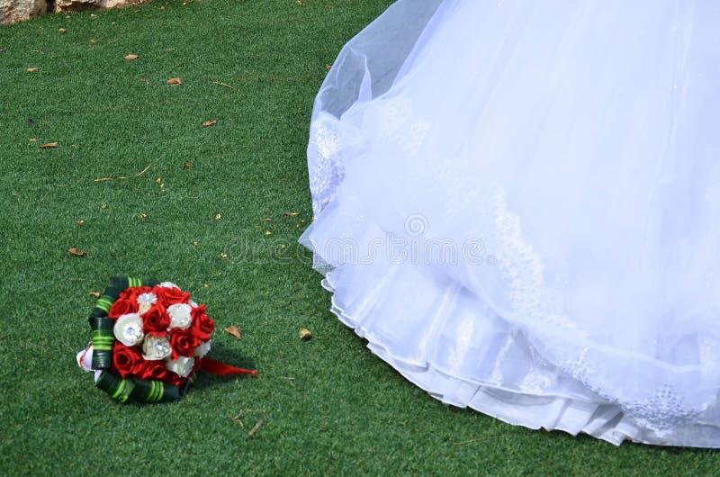 Bridal букет шарлаха и белых роз с зелеными листьями и кромкой платья свадьбы на траве стоковое изображение