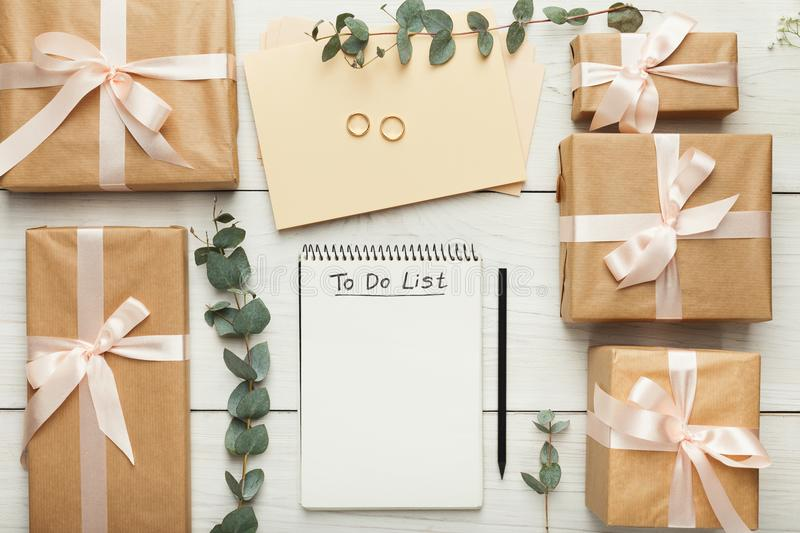 Bridal background with planner checklist. Wedding background with checklist. Paper planner and craft envelopes on white wooden table with lots of tender bridal stock photo