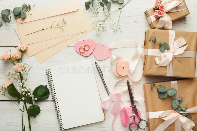 Bridal background with planner checklist. Wedding background with checklist. Paper planner and craft envelopes on white wooden table with lots of tender bridal stock image