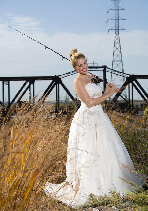 Bridal Beauty With Fishing Pole. Beautiful Blond model wearing elegant bridal gown posing with fishing pole in field on sunny day royalty free stock photos