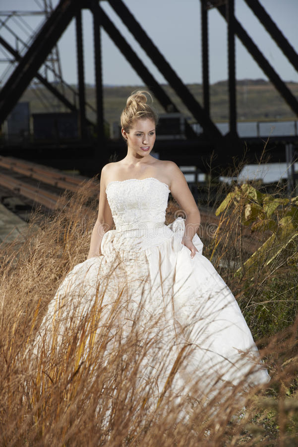 Bridal Beauty With Fishing Pole. Beautiful Blond model wearing elegant bridal gown posing with fishing pole in field on sunny day stock photo