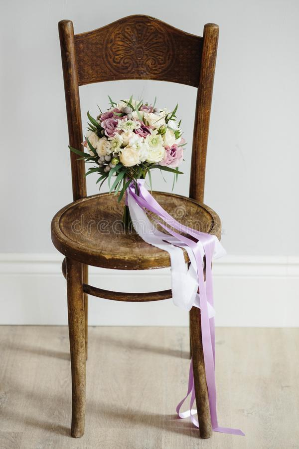 Bridal bouquet. Beautiful of white flowers and greenery, on vintage wooden chair stock images