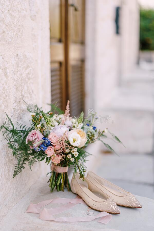 Bridal bouquet of cream roses, pink peonies, eustoma, waxflower, astilbe, limonium, branches of eucalypt tree, mattiola. Asparagus with cream ribbons near door royalty free stock image