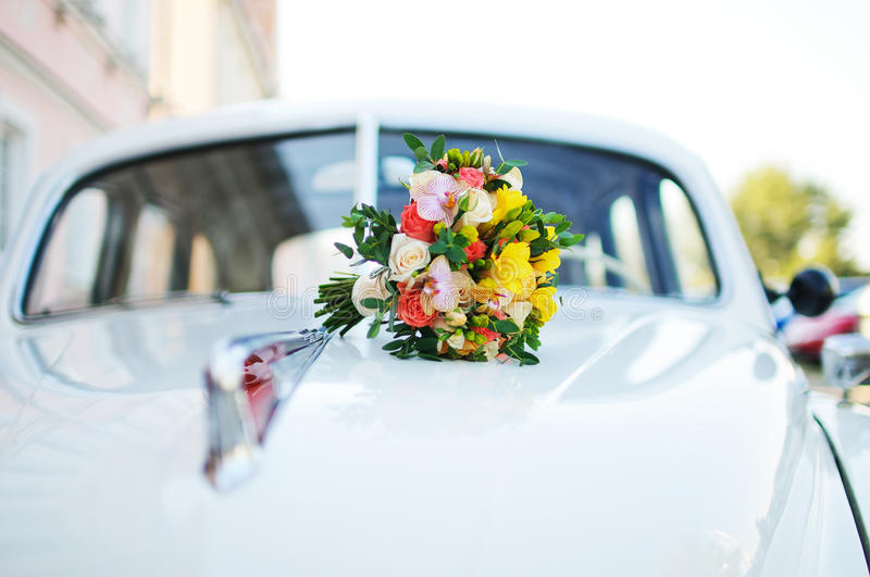 Bridal bouquet on the hood of the vehicle retro stock images