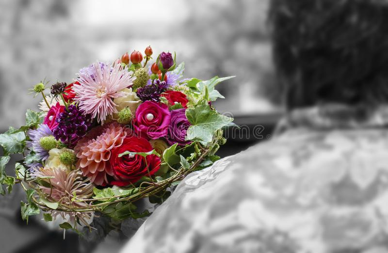 Bridal bouquet with pink and red blossom. The bridal throw the bridal bouquet over her shoulder royalty free stock images
