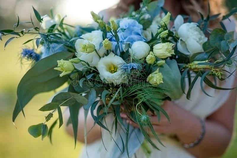 Bridal bouquet. Wedding bouquet in the hands of the bride. Outdoor shot in evening. Wedding bouquet in the hands of the bride. Outdoor shot in evening. Rustic stock photography