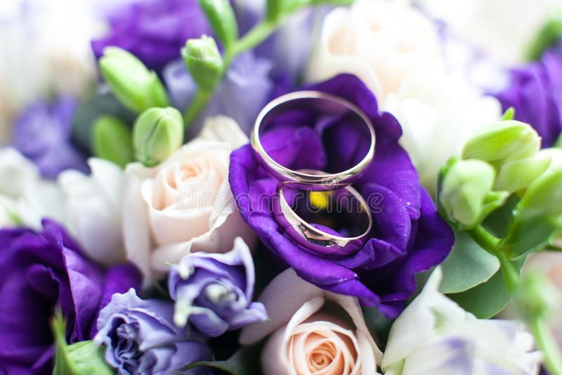 Bridal bouquet. Wedding rings on purple flowers stock photos