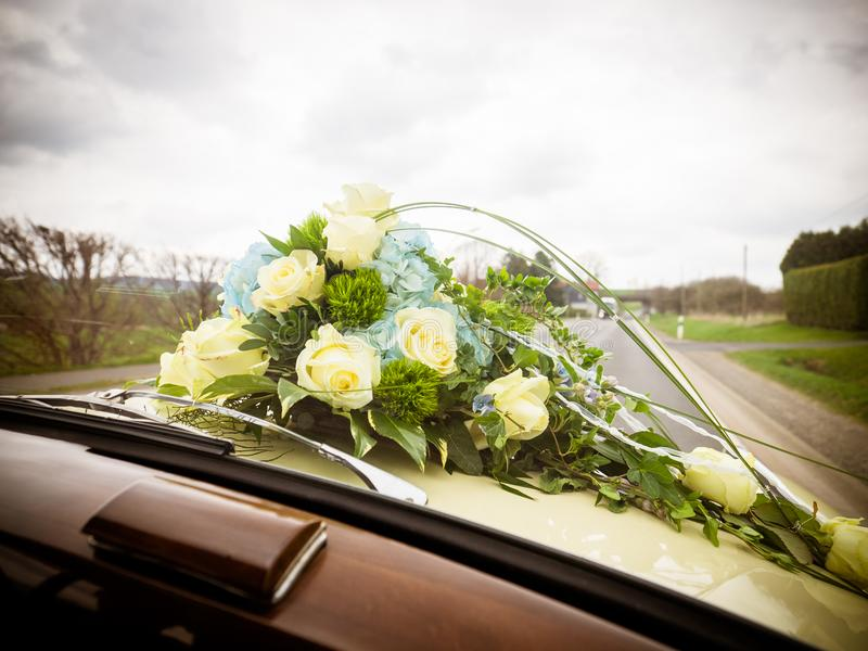 The bridal bouquet with white and blue roses on the bonnet. The bridal bouquet with white and blue roses lying on the bonnet stock images
