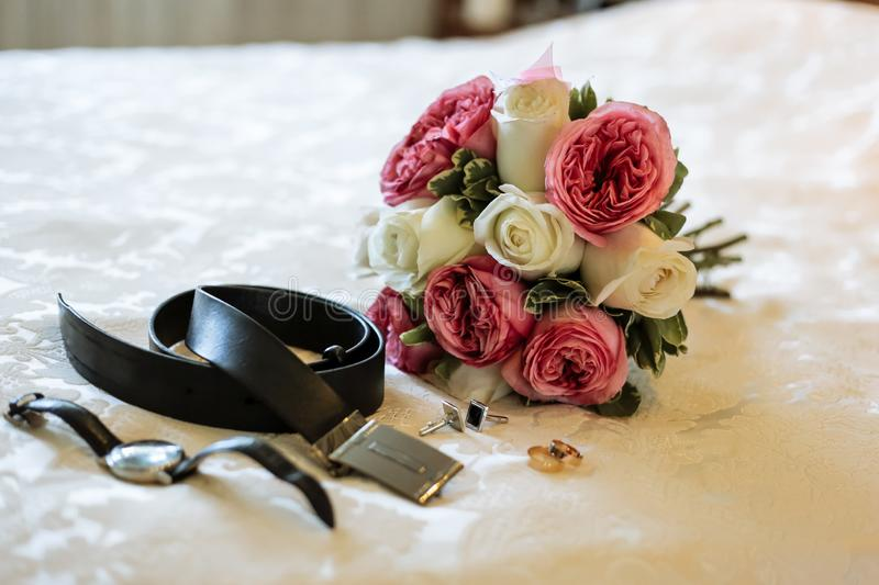 Bridal bouquet of white and pink roses, men`s belt, cufflinks, wedding rings, watches stock image