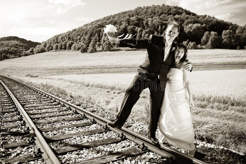 Bridal couple on rails, toned. Bridal couple on rails, being in the nature. Great azure sky. Great summer! He balances with one foot on the rail. Monochrome stock photography