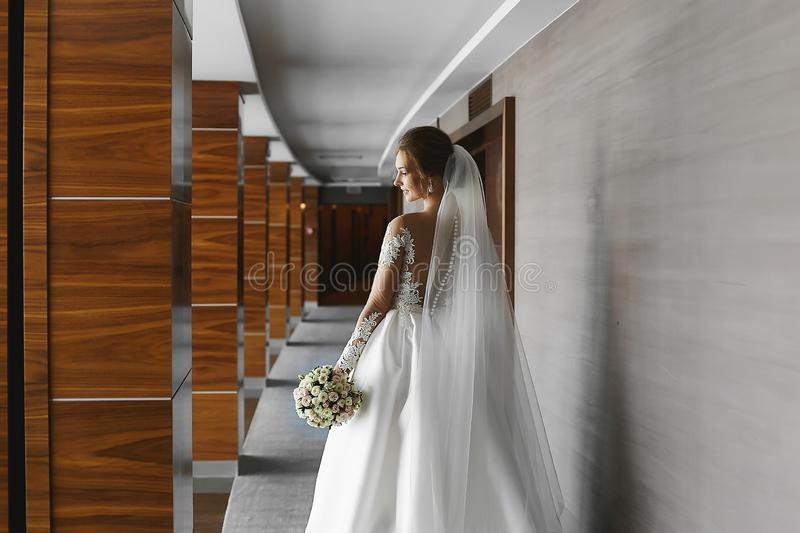 Bridal fashion model with perfect body in fashionable wedding dress posing with a bouquet of flowers in the interior. Beautiful young woman with wedding royalty free stock image