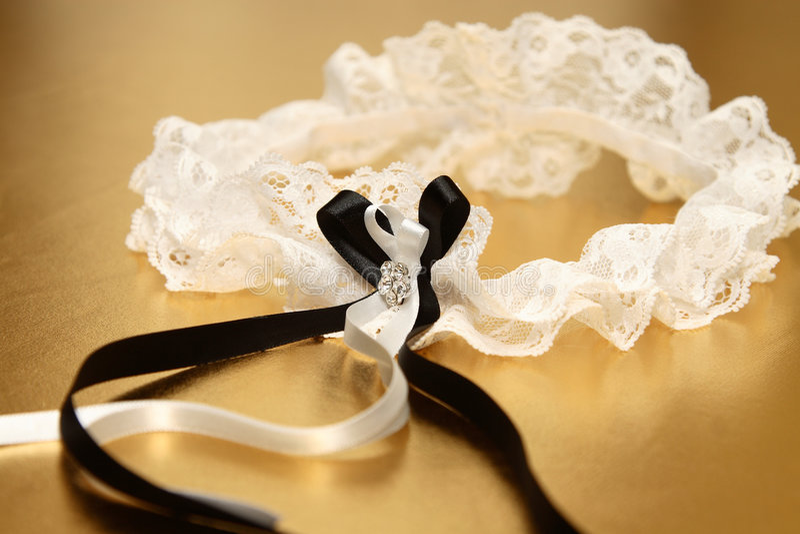 Bridal Garter. Cream lace bridal garter with black and cream ribbon royalty free stock photo