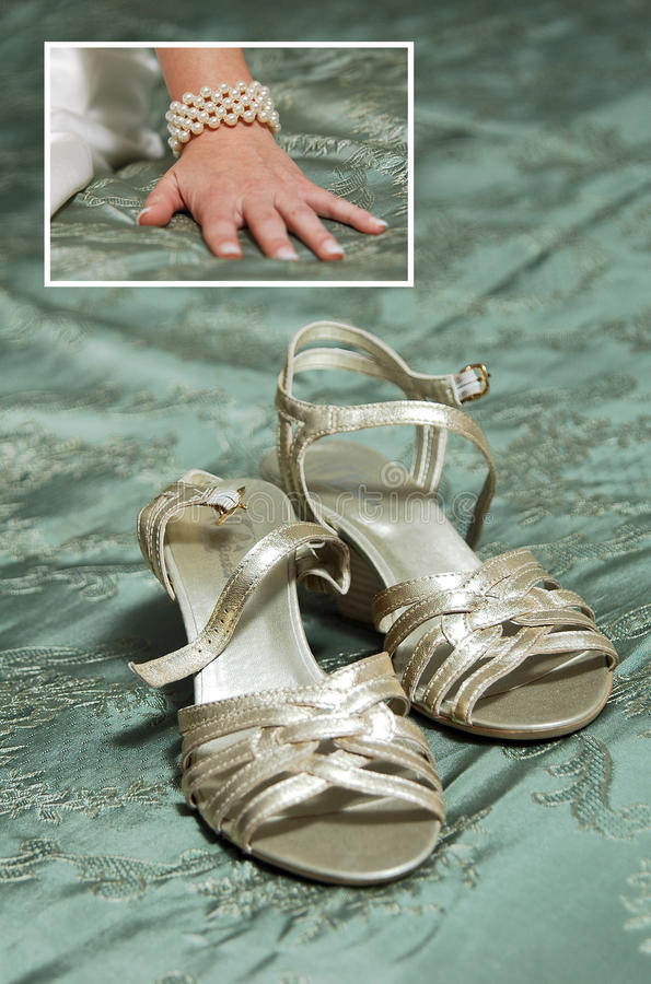 Bridal hand on the bed and wedding shoes stock photos