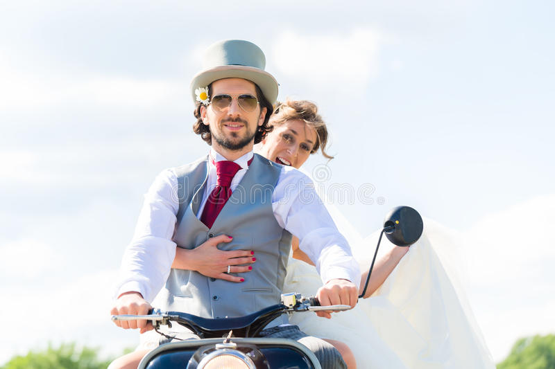 Bridal pair driving motor scooter wearing gown and suit. Wedding groom and bride driving motor scooter having fun stock image