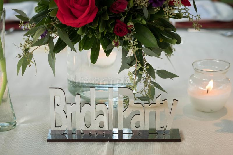 Bridal party chrome mirror sign at luxury wedding centerpiece decoration with natural flowers and roses stock photography
