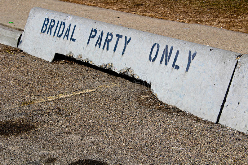 Bridal party only concrete jersey barriers in front of a hall.  royalty free stock photo