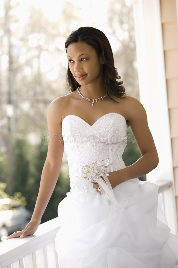 Bridal portrait. Portrait of African-American bride leaning against railing royalty free stock image