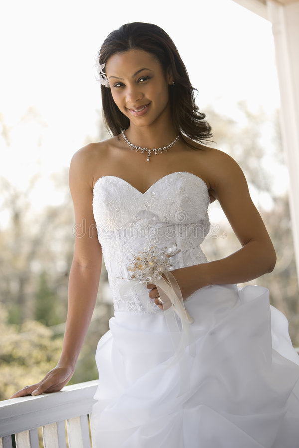 Bridal portrait. Portrait of African-American bride leaning against railing royalty free stock images
