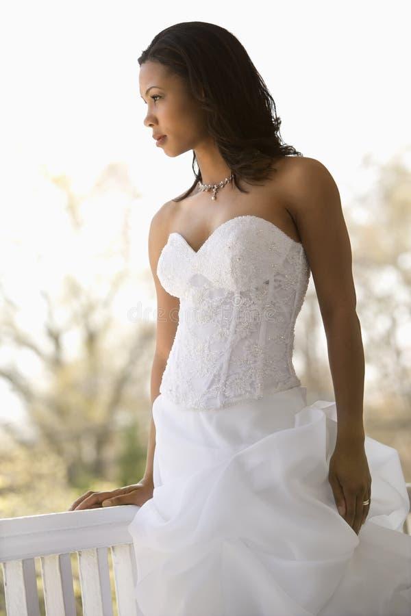 Bridal portrait. Portrait of African-American bride leaning against railing stock photos