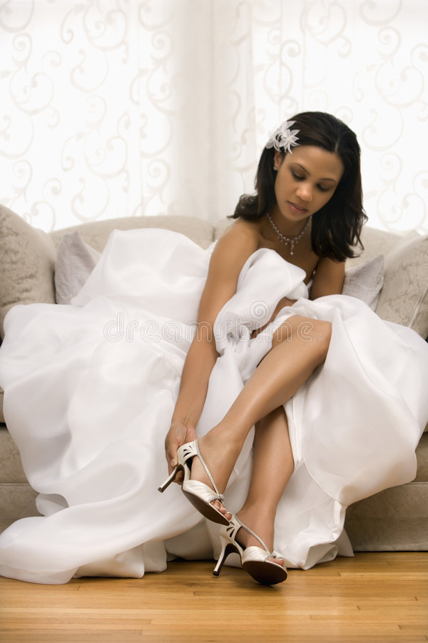 Bridal portrait. African-American bride placing shoe on foot royalty free stock photography