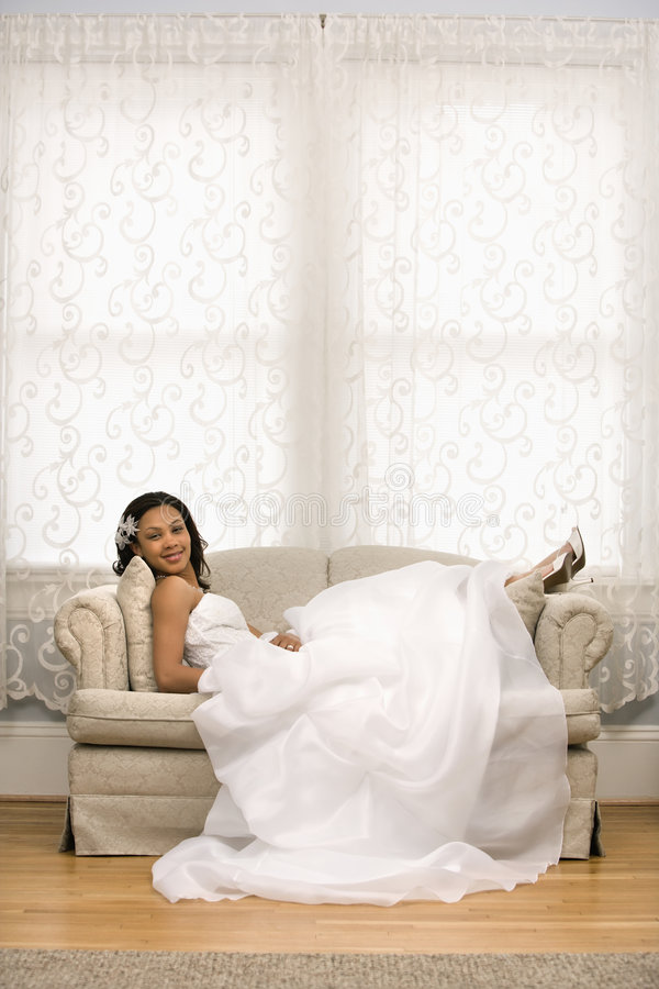 Bridal portrait. African-American bride lying on love seat stock image