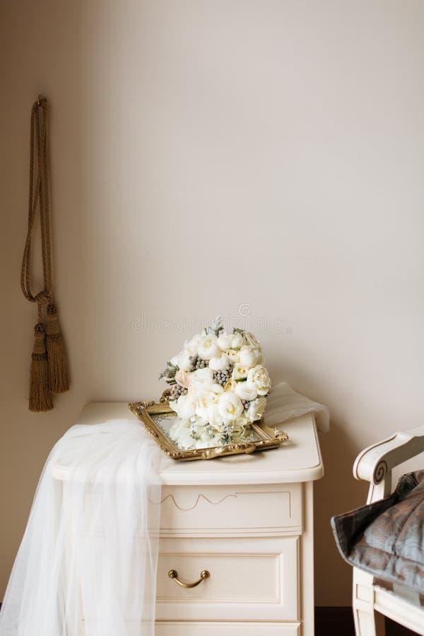 Bridal ranku wewnętrzny skład z białą przesłoną, ślubnym bukietem i nightstand, obraz stock