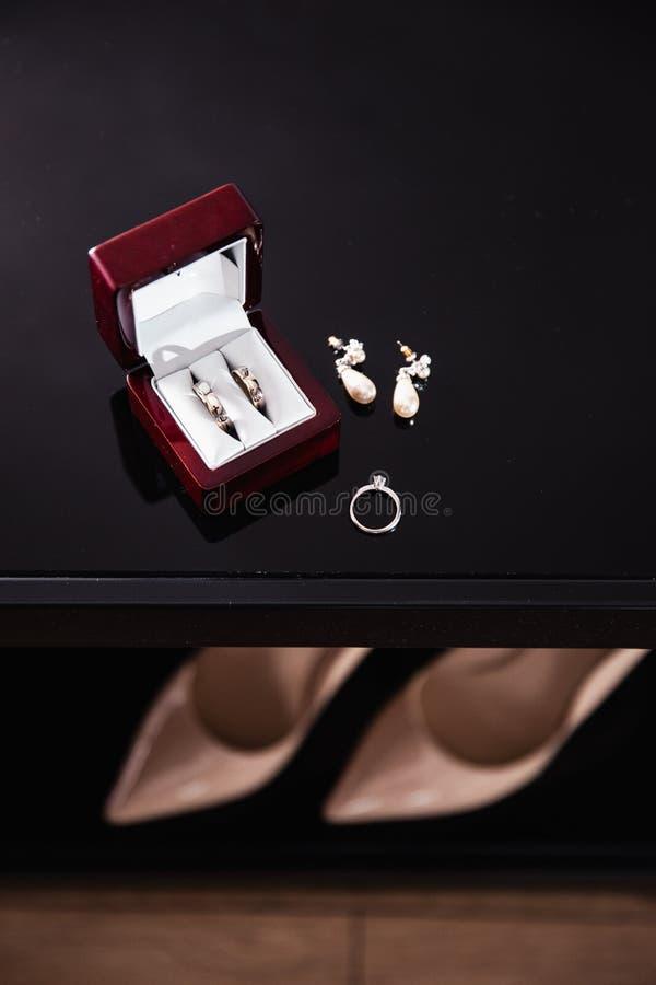 Bridal szczegóły kolczyki i buty z piętami są wewnątrz - obrączki ślubne podczas gdy panna młoda dostaje gotowy przed ceremonią - fotografia stock