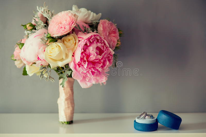 Bridal Wedding Bouquet with rings on a white table. Peonies Wedding Bouquet with wedding rings on a white table royalty free stock images