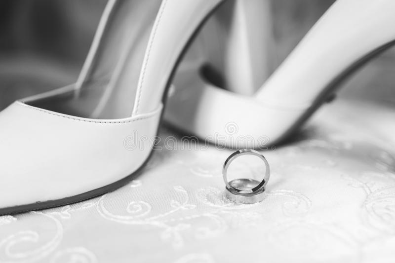 Bridal wedding shoes and rings on a white background. 2019 royalty free stock photography