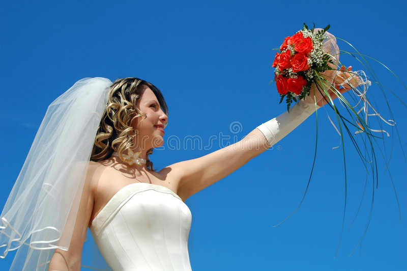 Bride. The happy bride with a bouquet of roses on a background of the sky stock image