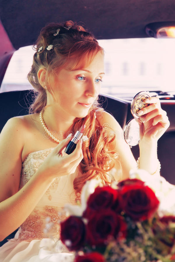 Bride. The bride sitting in the wedding car with lipstick and a pocket mirror in hands royalty free stock photography
