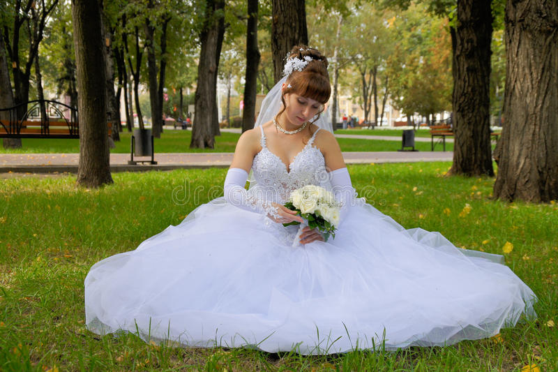 Bride. With bouquet sits on the grass in the park stock images