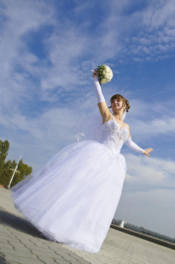 Bride. Beautiful bride with a bouquet of dancing against the sky royalty free stock image
