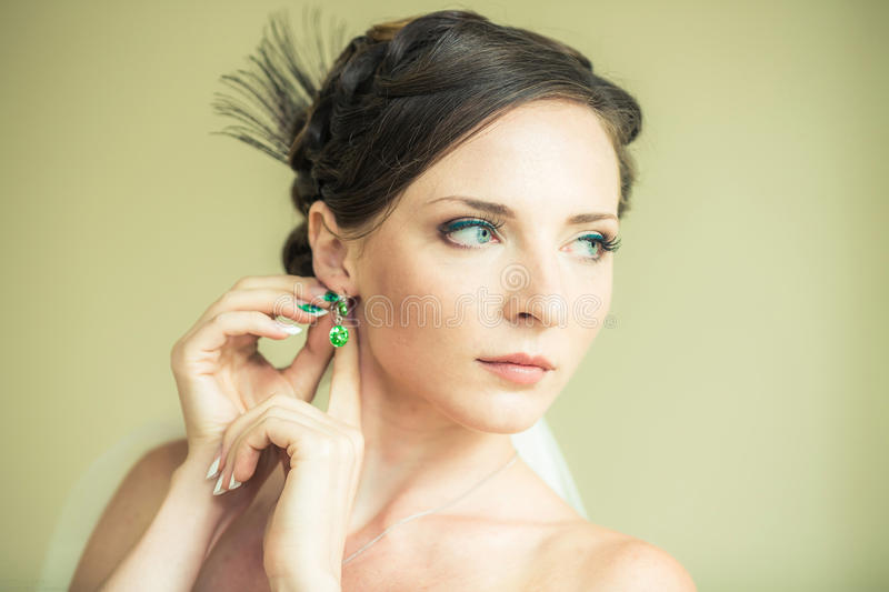 Bride. Is looking away and straightens earrings stock photos