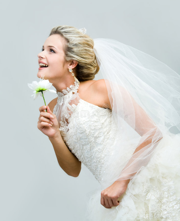 Bride. Profile of joyful bride with artificial flower looking straight and slightly upwards stock images