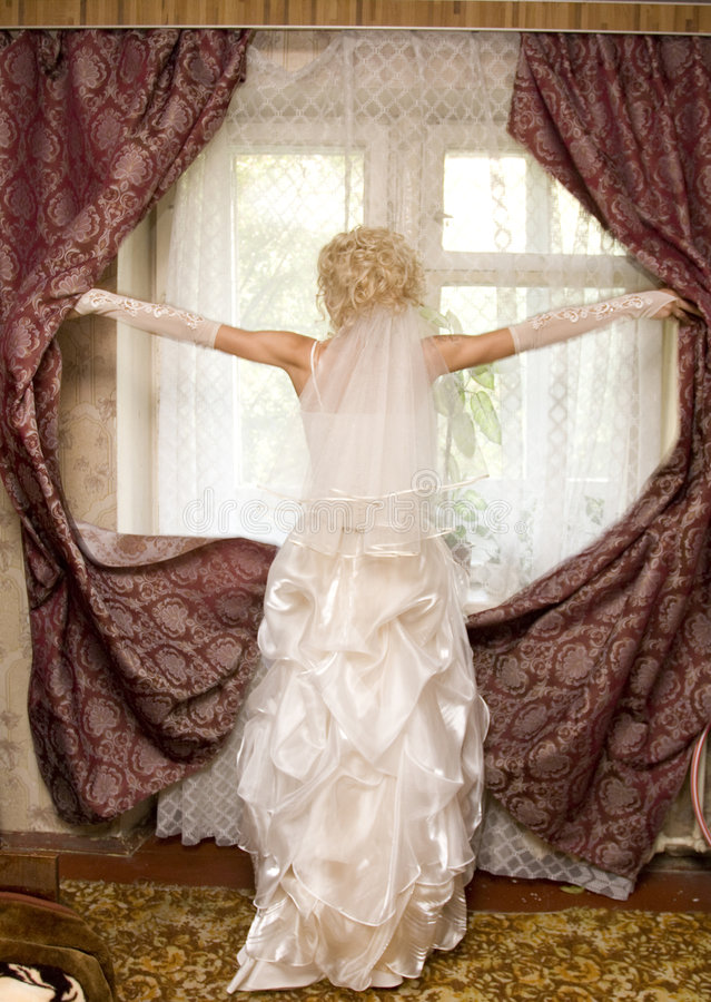 Bride. The beautiful bride prepares for wedding. Silhouette on a background of a window royalty free stock photos