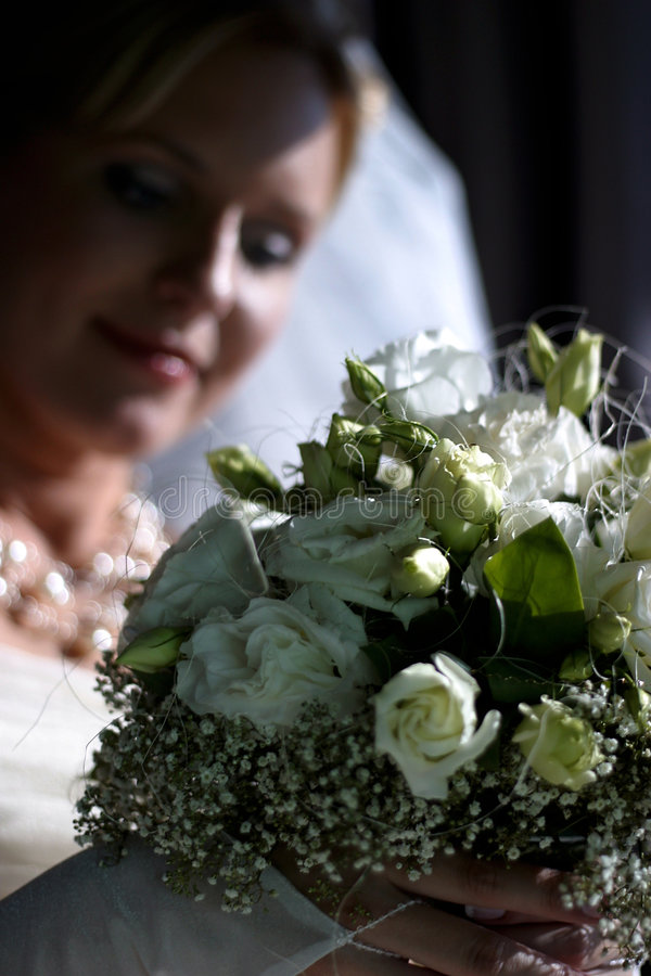 Bride. The bride with a bouquet from white roses. A bouquet in focus, the bride is dim stock photo
