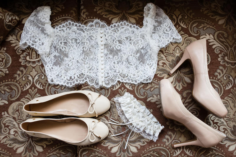 Bride accessories: lace blouse, garter, ballet flats, high-heeled shoes royalty free stock images