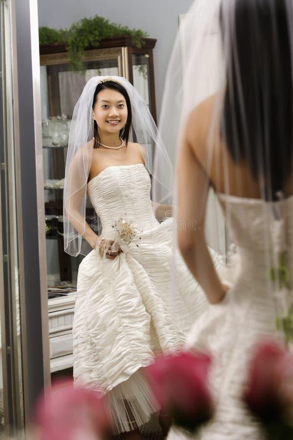 Bride admiring dress. stock images